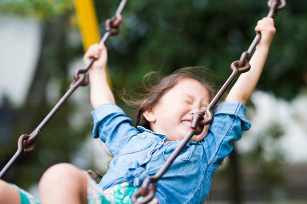 Niña jugando con un swing - foto de stock