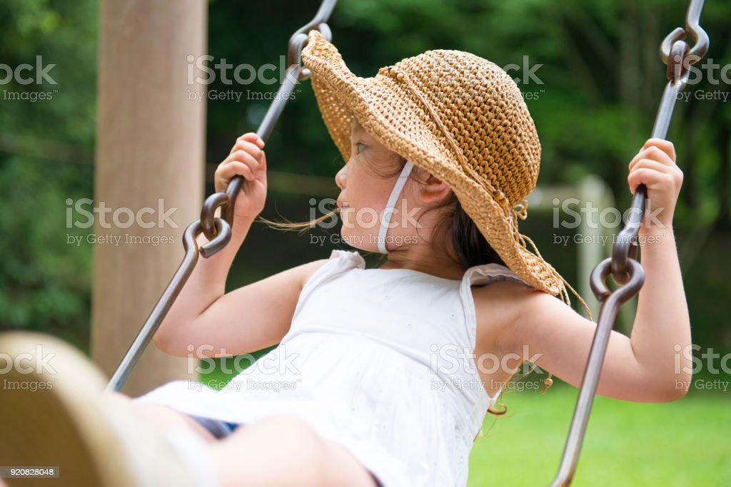 Little girl playing with a swing stock photo