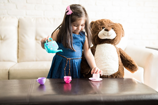 Portrait of cute little girl playing with a tea set on the table in living room, she is pouring tea in cups.