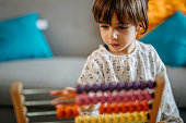 Photo of little girl playing with abacus at home