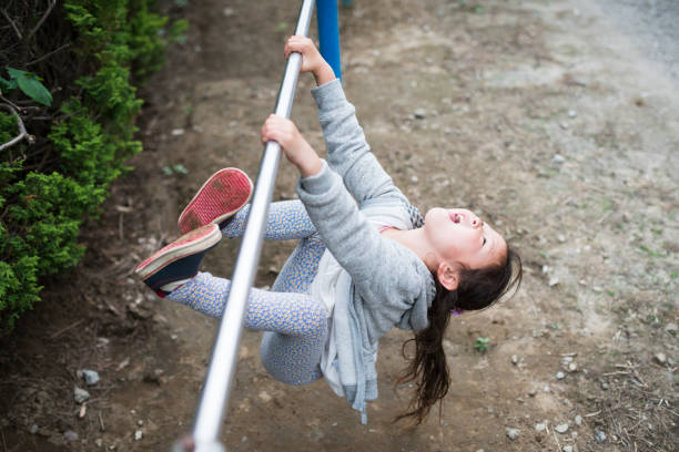 little girl playing with an iron bar - horizontal bar stock photos and pictures