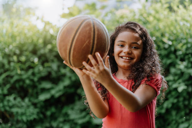 Little girl playing with basketball in the yard stock photo