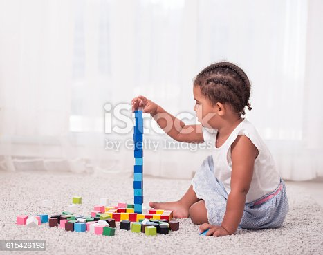 173937666istockphoto Little girl playing with block cubes. 615426198