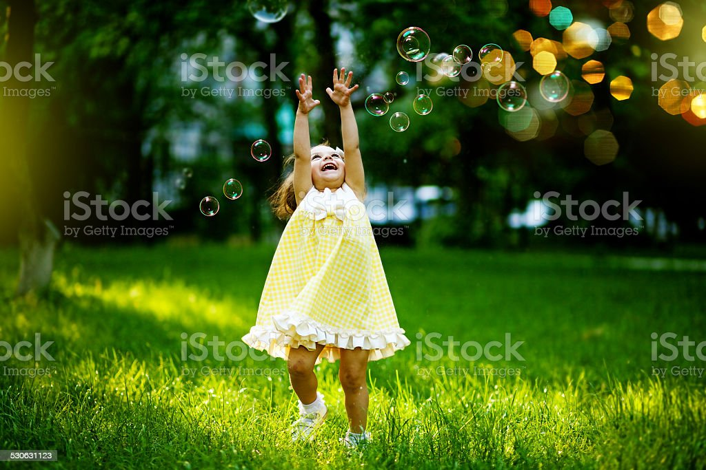 Little girl playing with bubbles stock photo