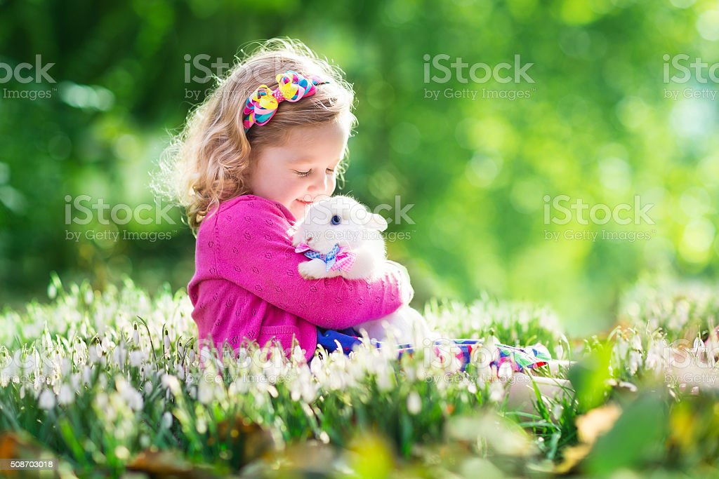Little girl playing with bunny on Easter egg hunt stock photo
