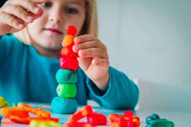 dziewczynka bawiąca się kształtami formowania gliny, rzemiosła dla dzieci - glina zdjęcia i obrazy z banku zdjęć