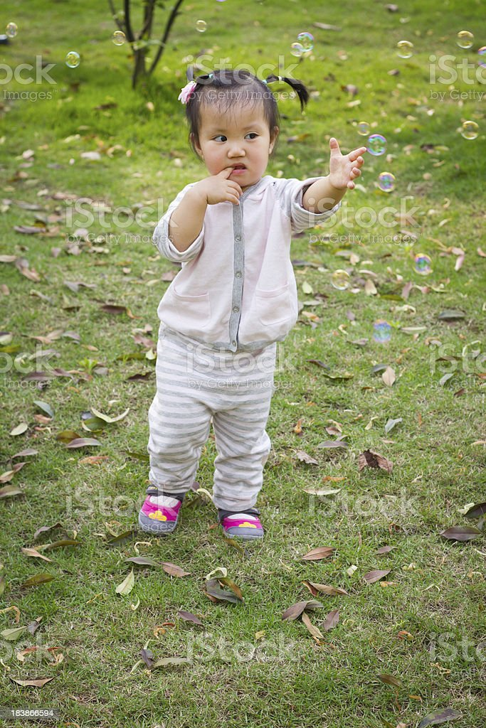 little girl playing with  colorful bubble stock photo