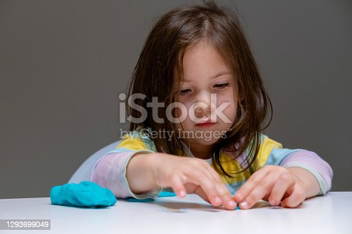 Little girl playing with colorful clay. Cute child girl sits at the table and plays with plastiline (Play dough) on gray background.
