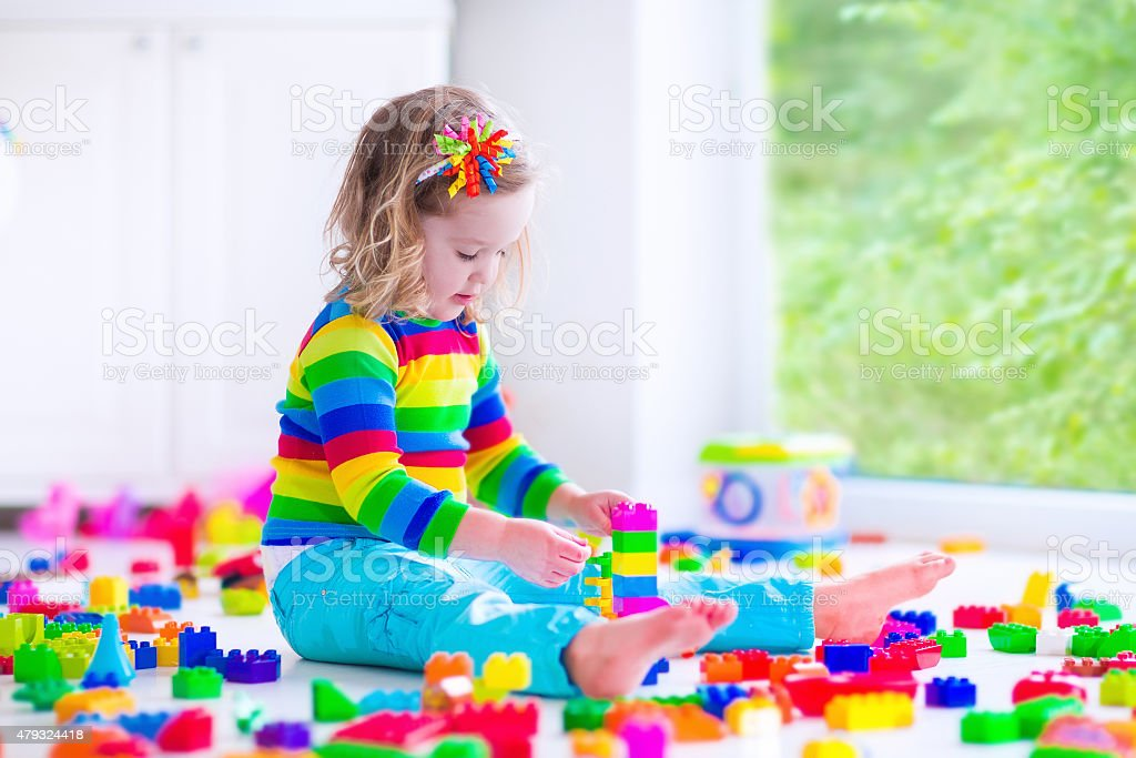 Little girl playing with colorful toy blocks stock photo