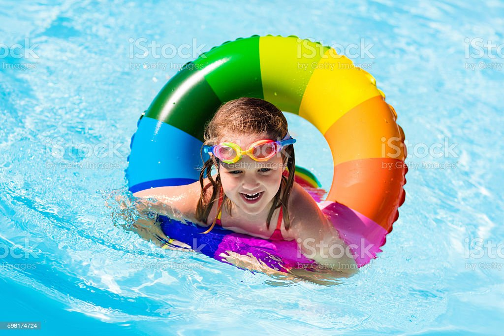Little girl playing with colorful toy ring in swimming pool stock photo