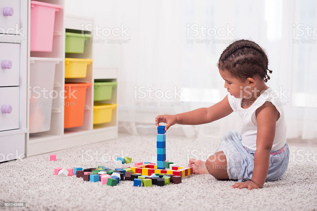 Little girl playing with cubes. stock photo