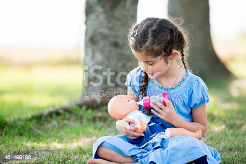 A little girl is sitting outside at the park on the grass, she is holding a doll and pretending to feed the doll with a bottle.