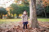 小さな女の子が落ち葉で遊んで
