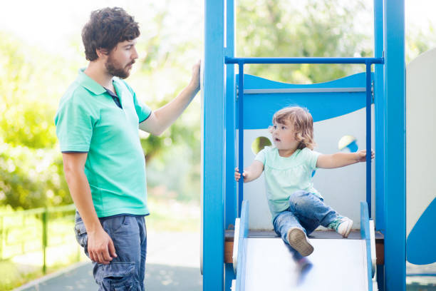 Little girl playing with her father on a playground. stock photo