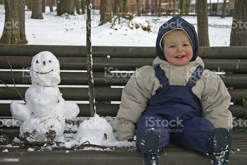 Little girl playing with her snowman royalty-free stock photo