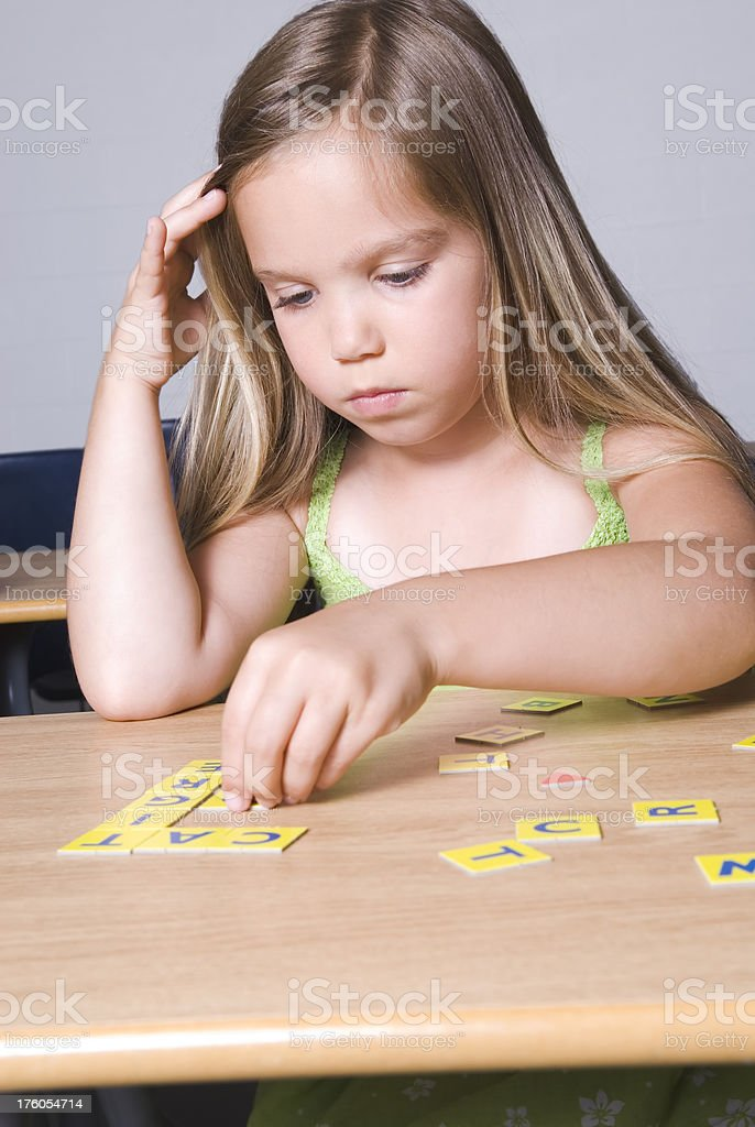 Little girl playing with letters in the classroom - I royalty-free stock photo