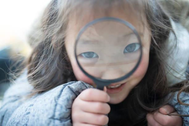 kleine mädchen spielen mit lupe - spiel des wissens stock-fotos und bilder