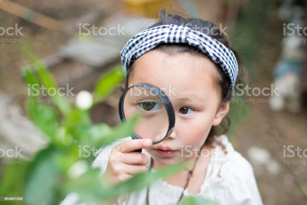 Little girl playing with magnifying glass Little girl playing with magnifying glass 6-7 Years Stock Photo