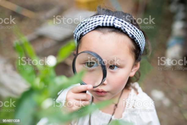 Little Girl Playing With Magnifying Glass Stock Photo - Download Image Now