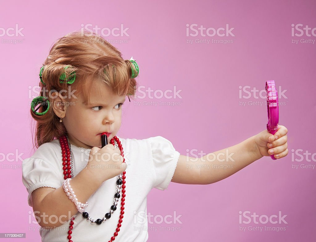 Little girl playing with mothers makeup royalty-free stock photo