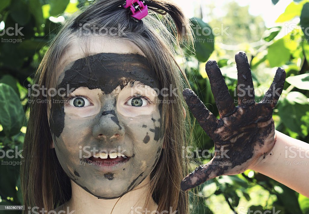 Little girl playing with mud in park. stock photo