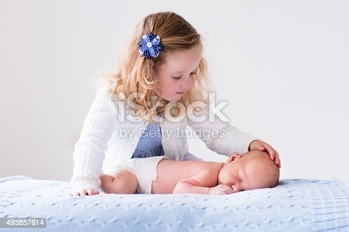 istock Little girl playing with newborn baby brother 493857614