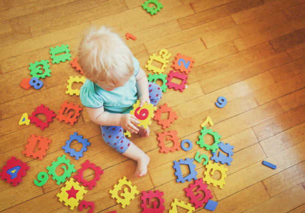 little girl playing with number puzzles stock photo