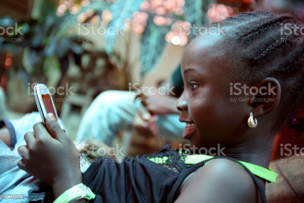 Little Girl Playing with Phone stock photo