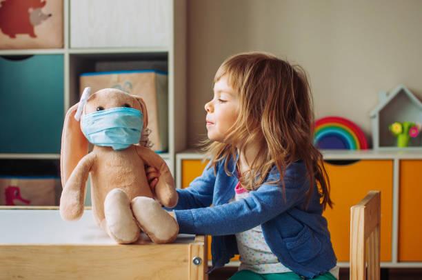 petite fille jouant avec le jouet doux de lapin dans le masque de médecine - masque enfant photos et images de collection