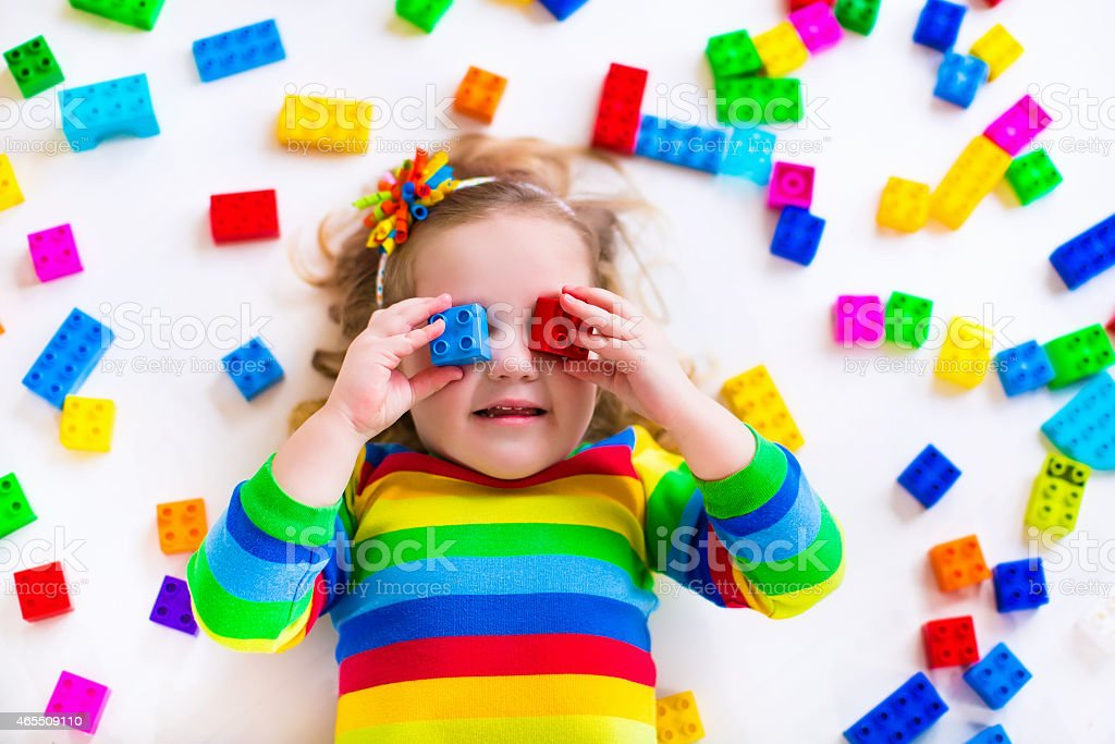 A little girl playing with rainbow legos stock photo