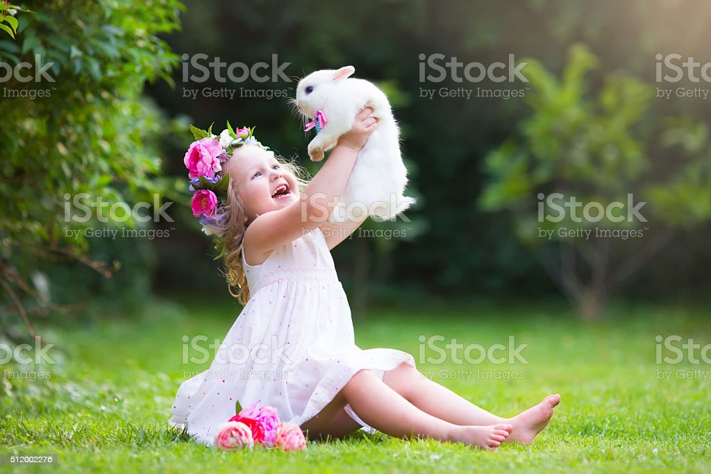 Little girl playing with real rabbit stock photo