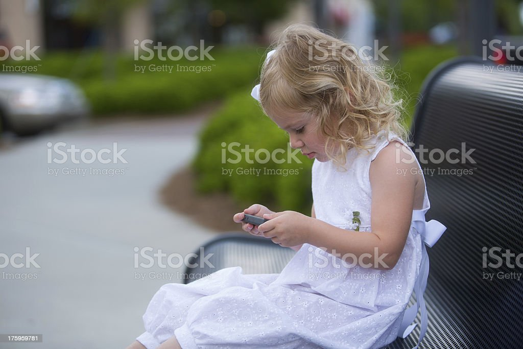 little girl playing with smartphone royalty-free stock photo