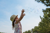 Little girl is chasing bubbles under blue sky