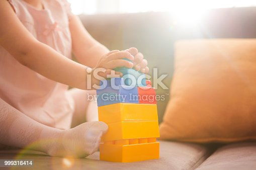 istock Little girl playing with toy blocks 999316414