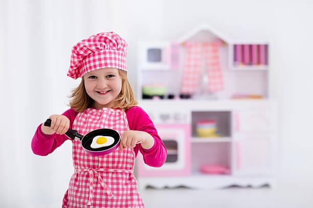 little girl playing with toy kitchen cooking fried eggs - chefkoch auflauf stock-fotos und bilder