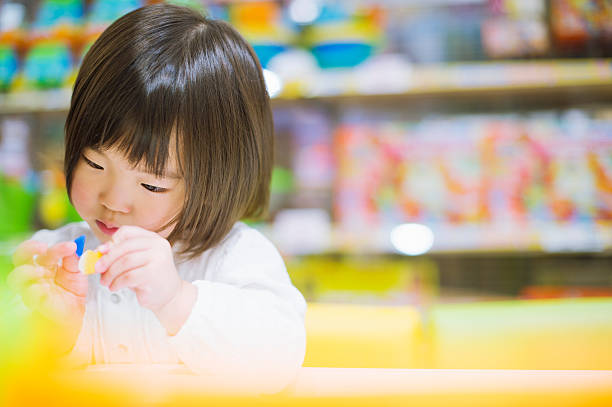 little girl playing with toys. - preschool building stock photos and pictures