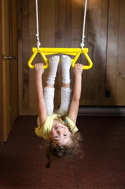 kleines mädchen spielt mit trapez im haus - trapez stock-fotos und bilder