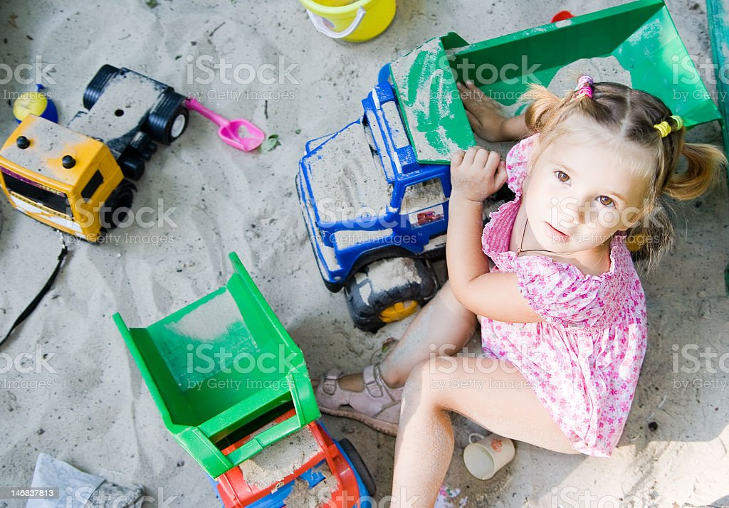Little girl playing with trucks in the sand stock photo