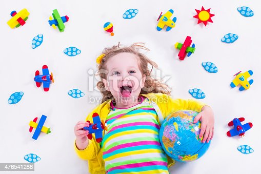 istock Little girl playing with wooden airplane and globe 476541288