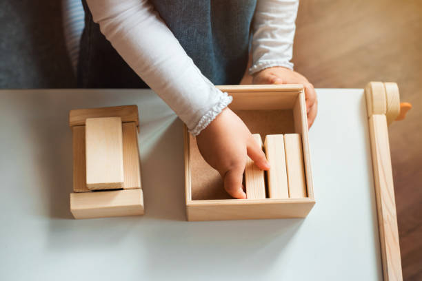Little girl playing with wooden bricks at home. Little girl playing with wooden bricks at home. She builds little house. kids cleaning up toys stock pictures, royalty-free photos & images