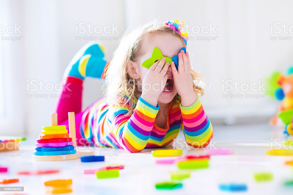 Little girl playing with wooden toys stock photo