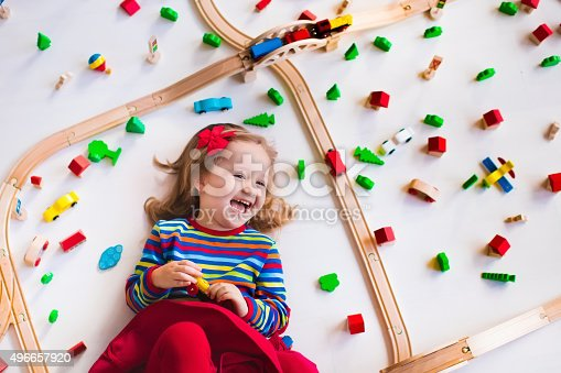 istock Little girl playing with wooden trains 496657920