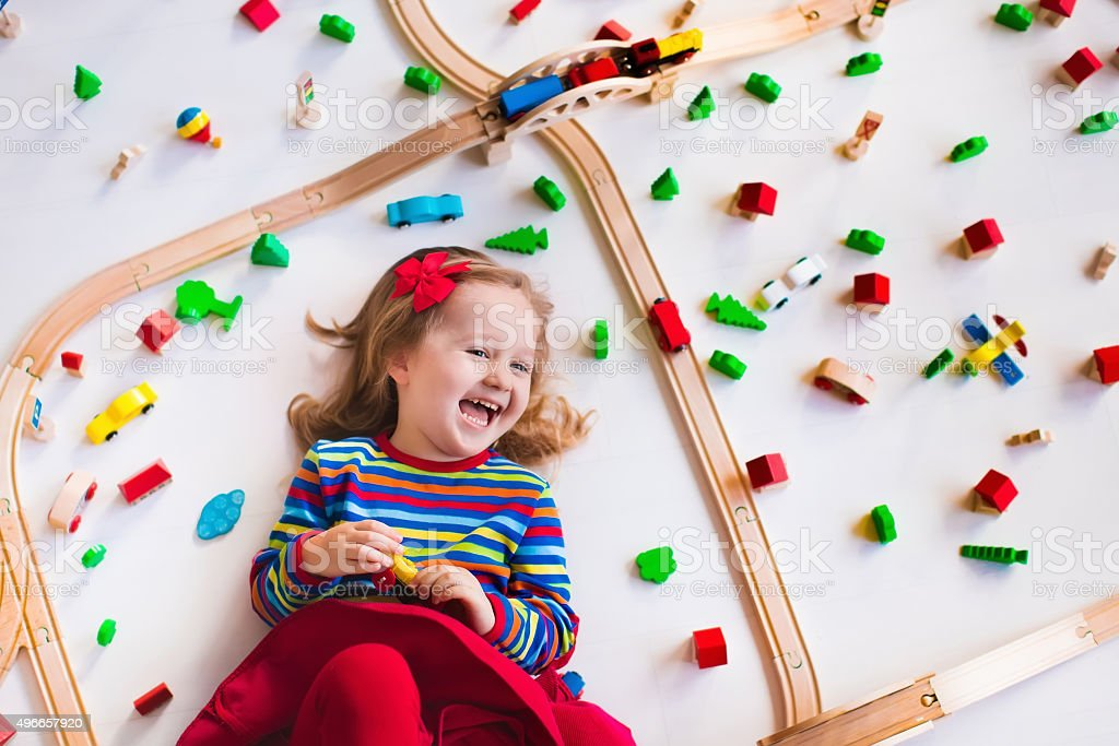 Little girl playing with wooden trains stock photo