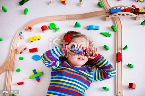 500939056 istock photo Little girl playing with wooden trains 496662718