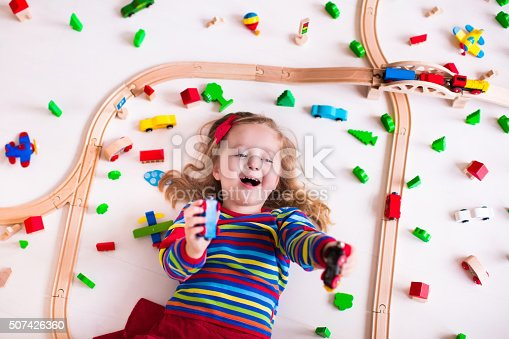 500939056 istock photo Little girl playing with wooden trains 507426360