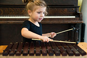 Little girl playing xylophone with piano in background, horizontal.
