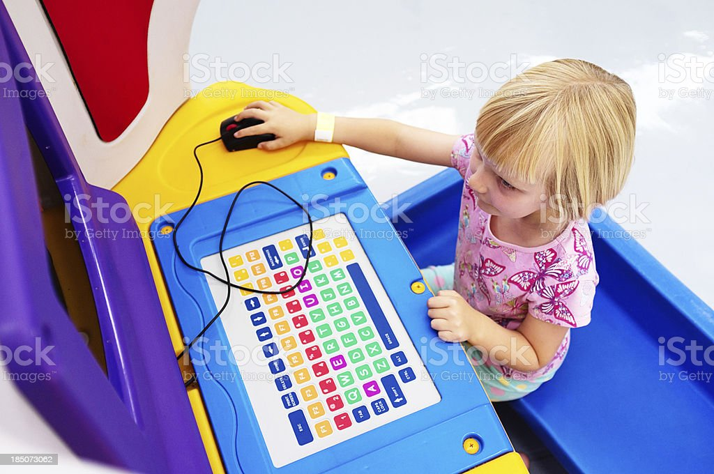 Little girl plays on colorful giant computer concentrating happily stock photo