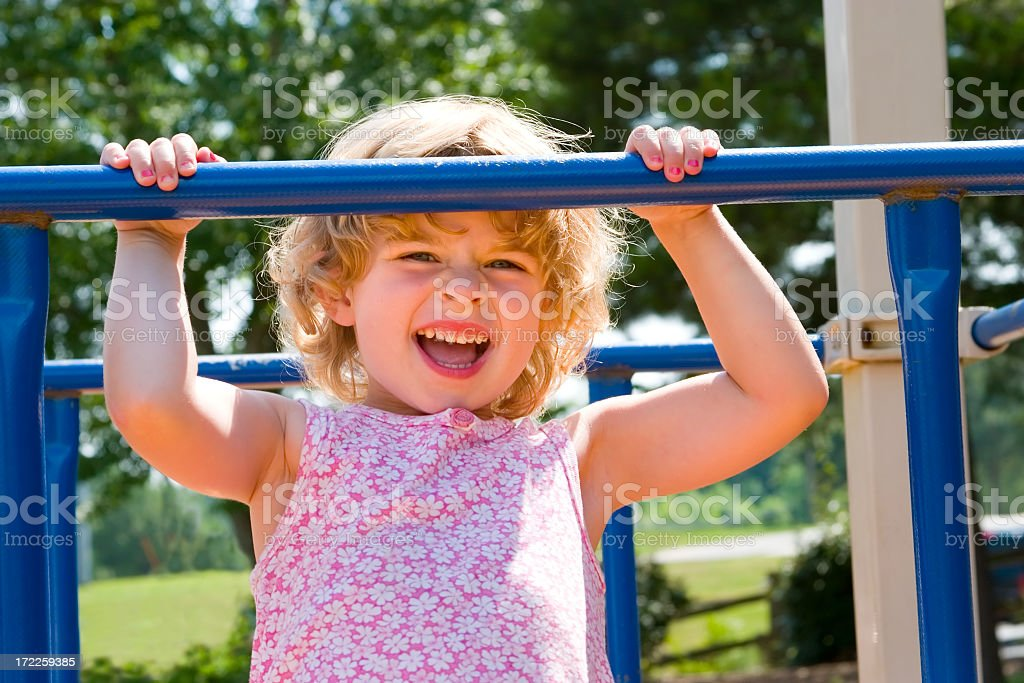 Little girl plays on playground. stock photo