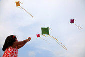Little girl raises a kite in a sky where some other kites are also flying
