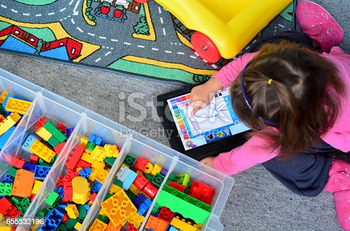 istock Little girl plays with touch screen computer 655532196